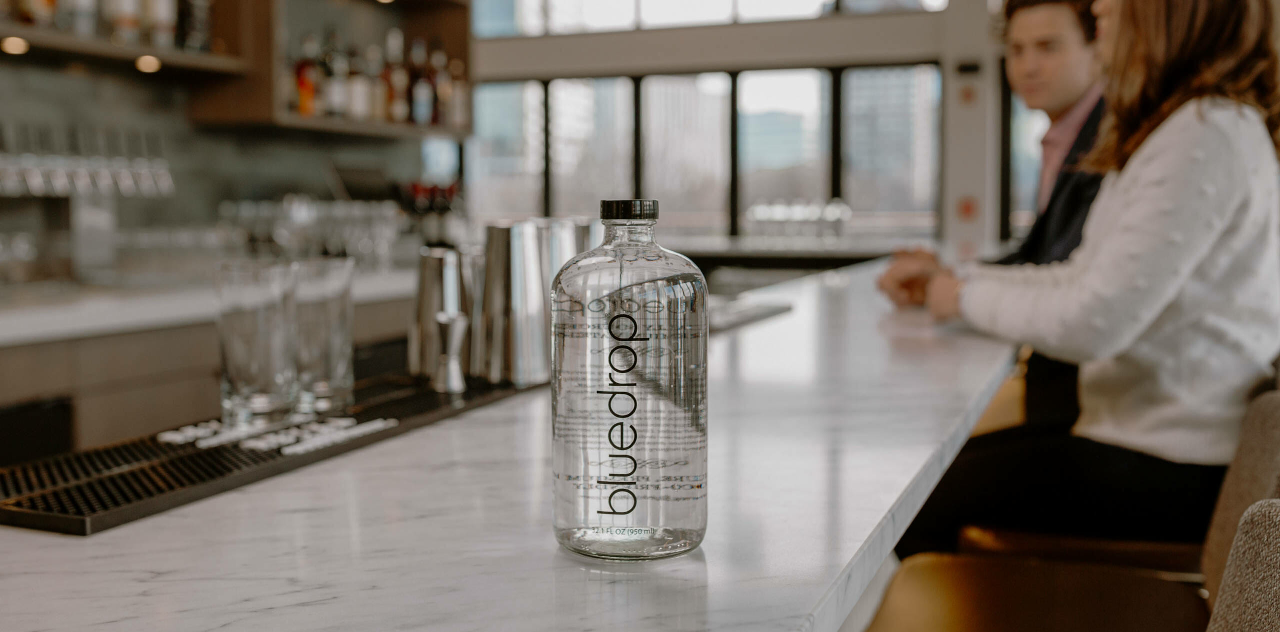 A bluedrop bottle of water sitting on a counter at a bar or restaurant.