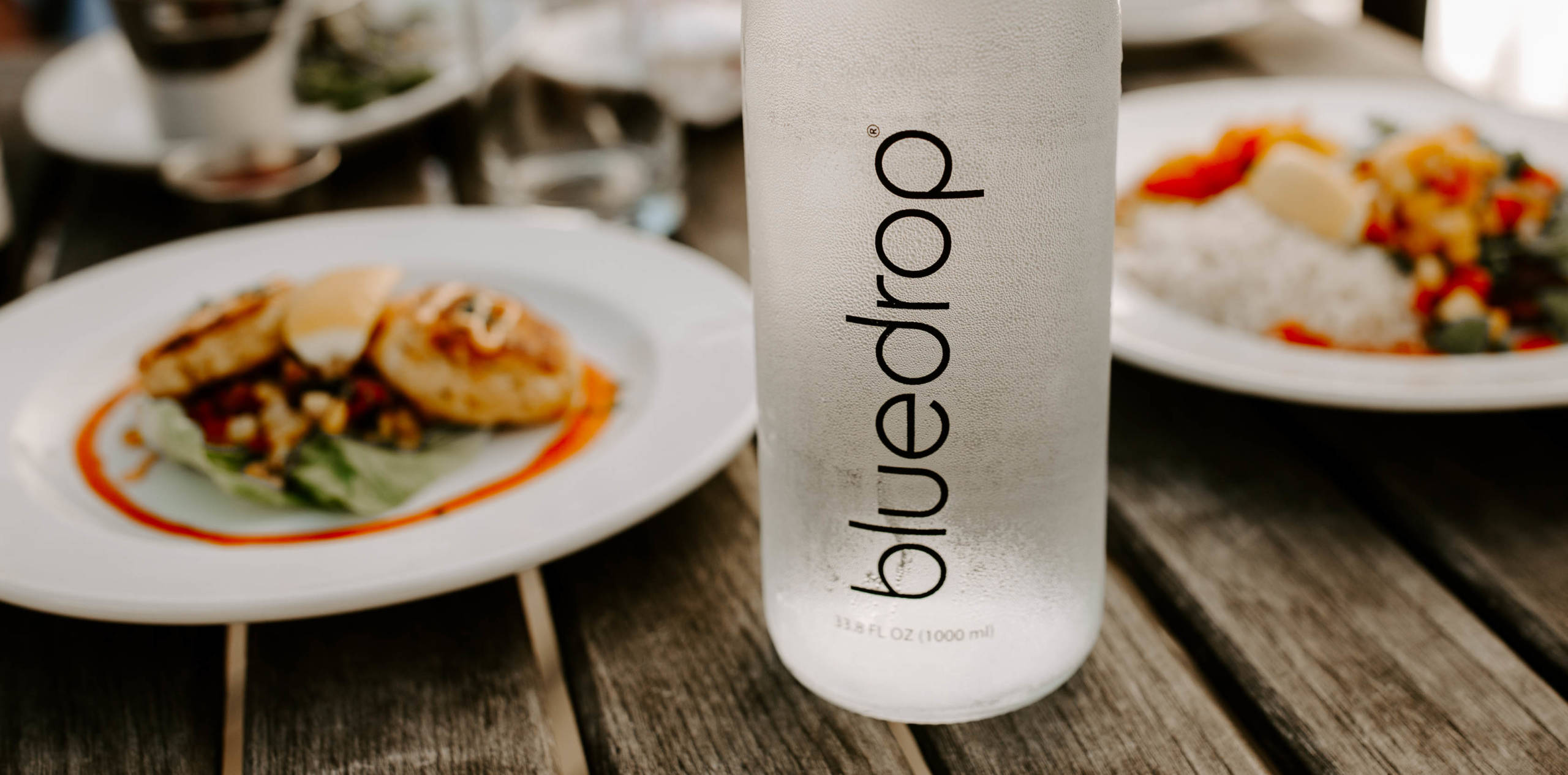 A bottle of bluedrop water on a table at a restaurant.