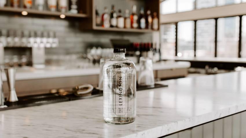 A lexington branded glass bottle on a bar counter.