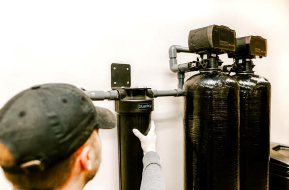 A person installing or adjusting their bluedrop water filtration system.