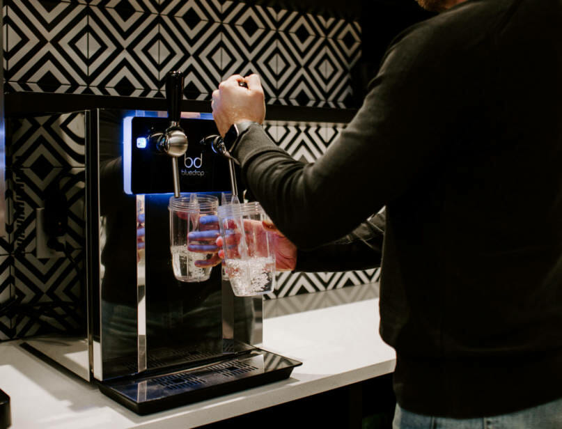 A person using the bluedrop water system to fill a glass of water.