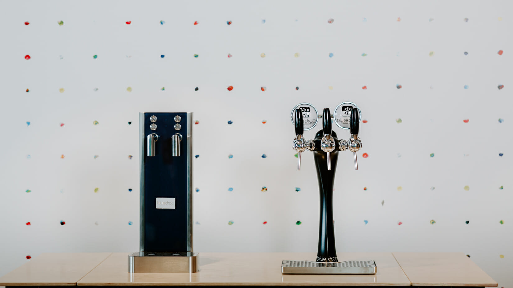 A bluglass tower and a black tower next to each other on a counter.