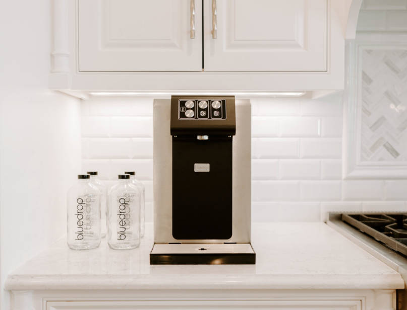 A home still and sparkling water system on a kitchen counter.
