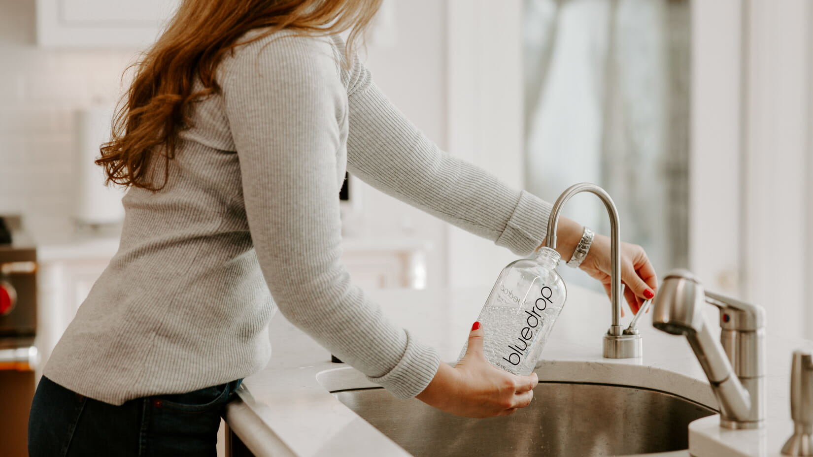 A person filling their water bottle with water from the sink.