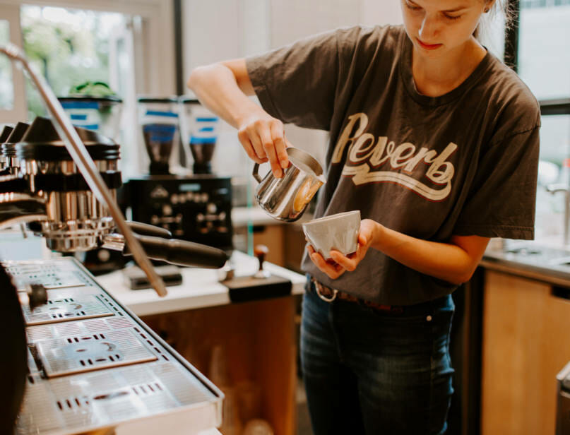 A barista making a latte.