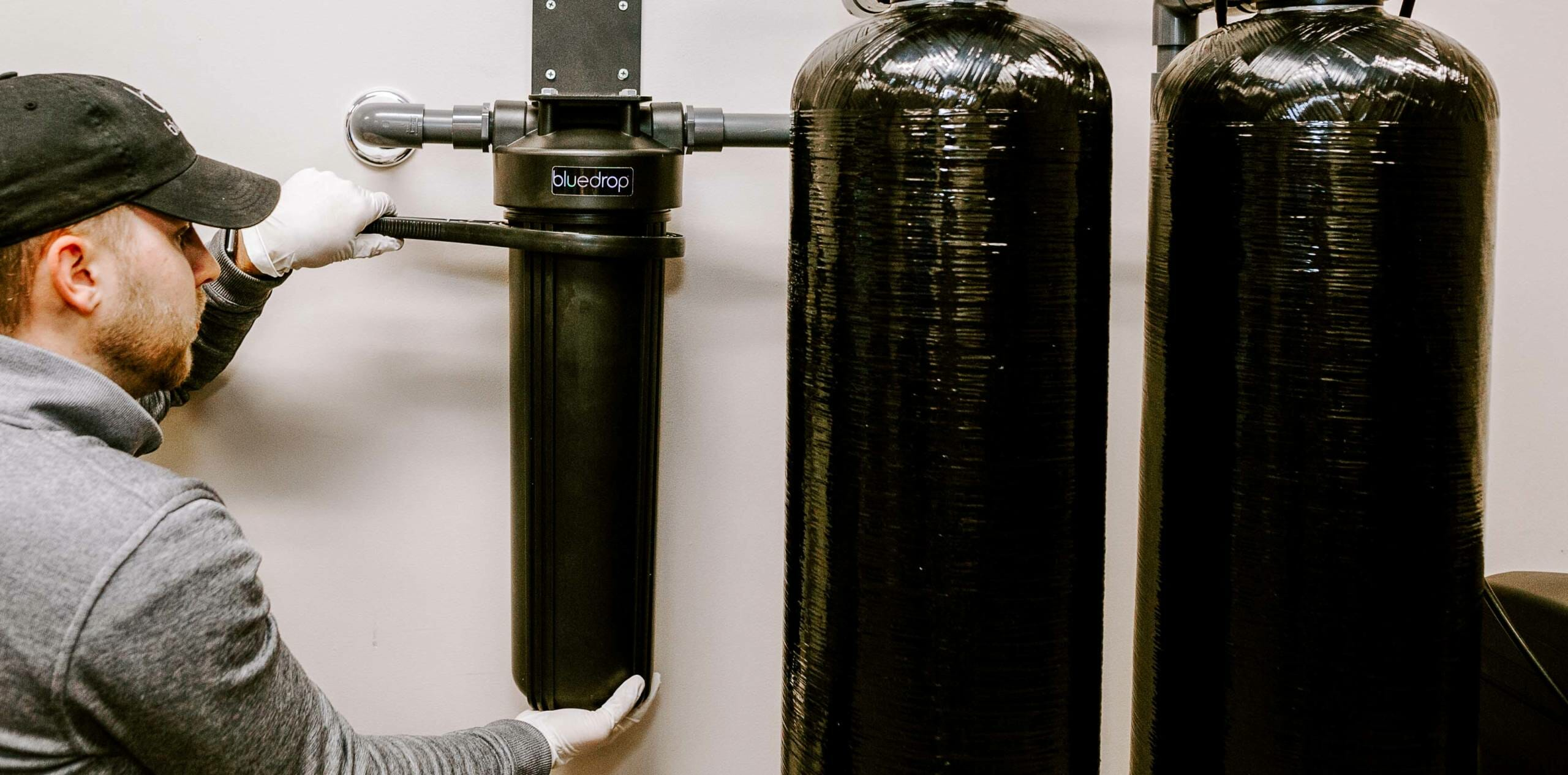 A person adjusting their bluedrop water whole home filtration system.